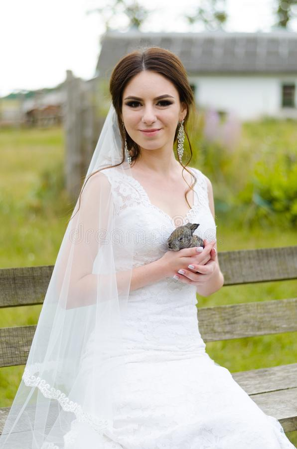 Young woman bride smiling and holding cute rabbit over park summer nature outdoor. White wedding dress, green background stock photos