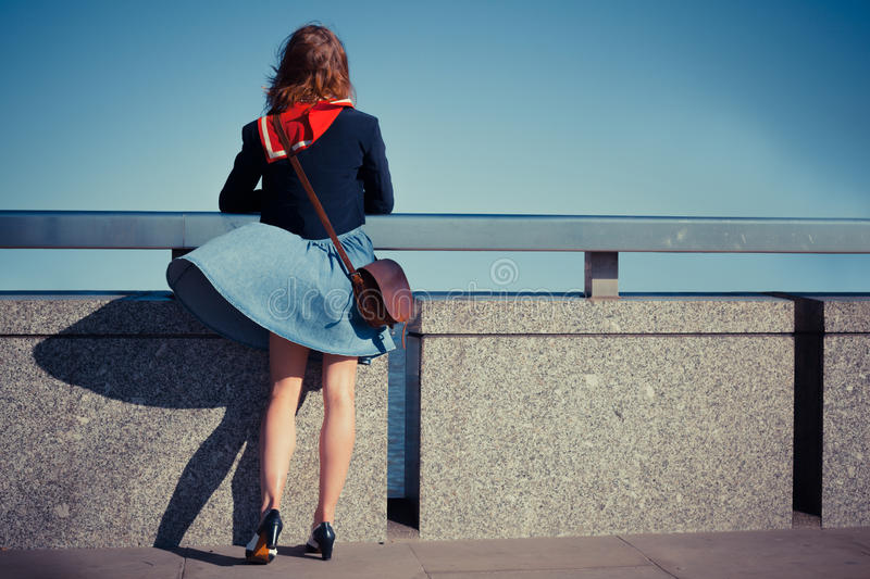 Young woman on bridge with skirt blowing. A young woman is standing on a bridge with her skirt blowing in the wind stock photos