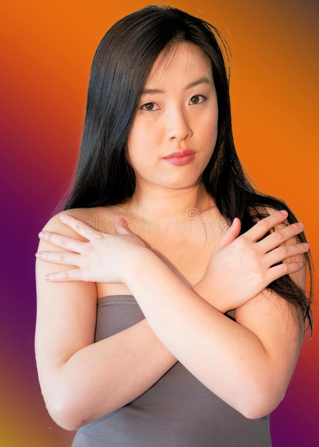 Young woman with bright colored background crosses her bare arms over chest stock photo