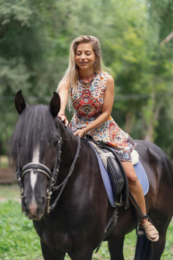 Young woman in a bright colorful dress riding a black horse. In the park royalty free stock photo