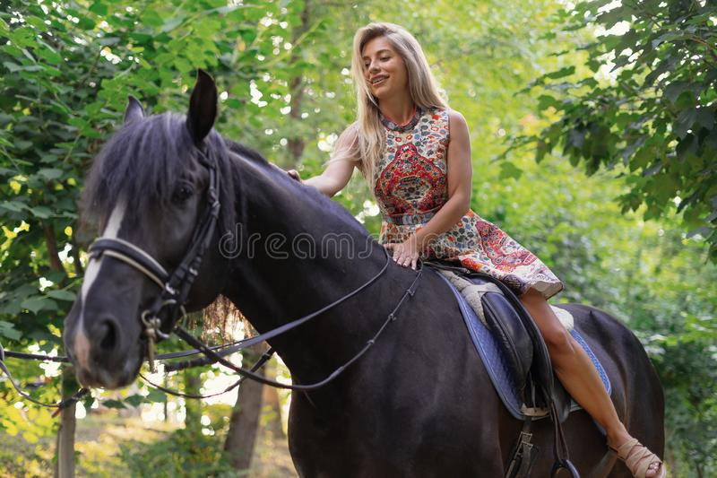 Young woman in a bright colorful dress riding a black horse. In the park stock photo
