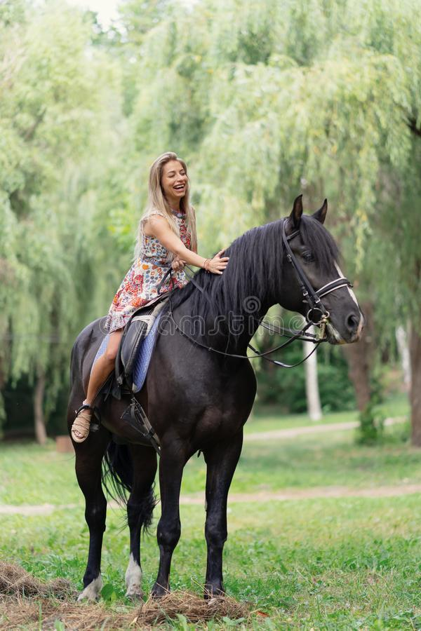 Young woman in a bright colorful dress riding a black horse. In the park stock images