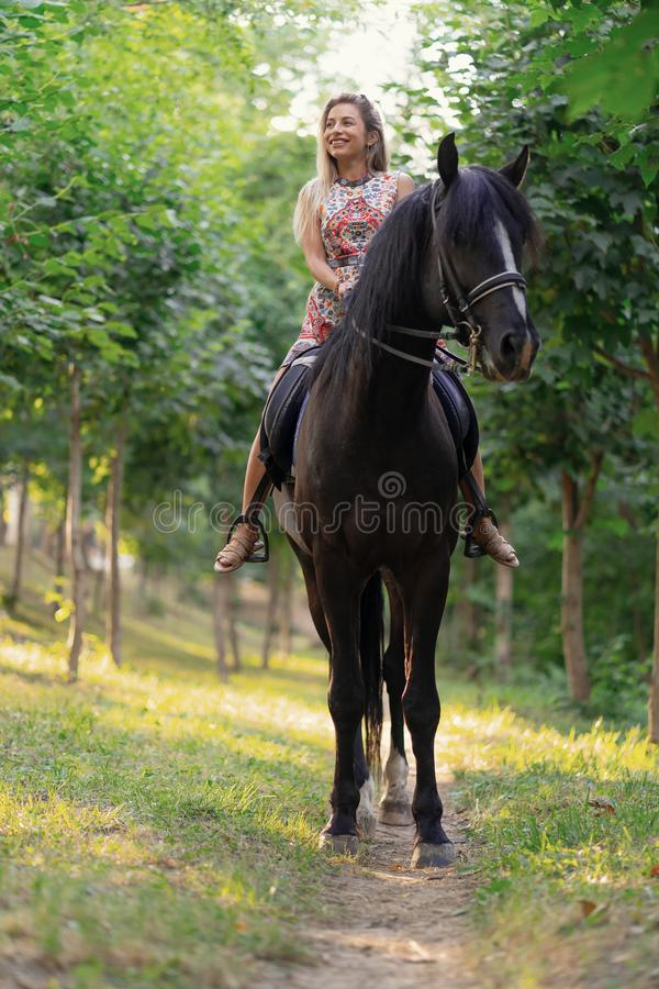 Young woman in a bright colorful dress riding a black horse. In the park royalty free stock photography