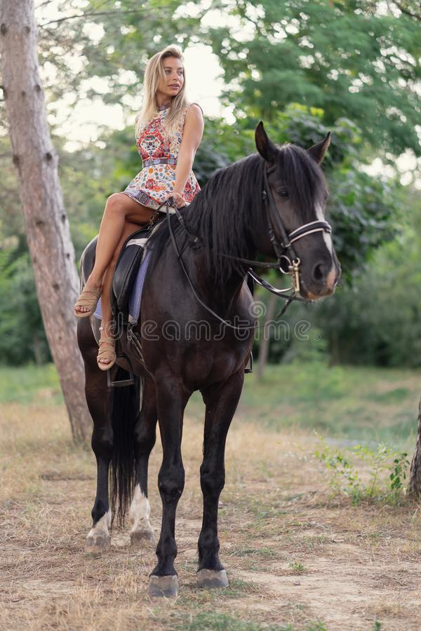 Young woman in a bright colorful dress riding a black horse. In the park royalty free stock images