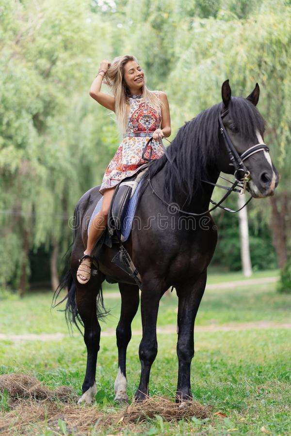Young woman in a bright colorful dress riding a black horse. In the park stock photos