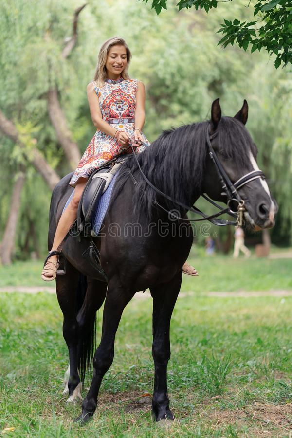 Young woman in a bright colorful dress riding a black horse. In the park stock photography