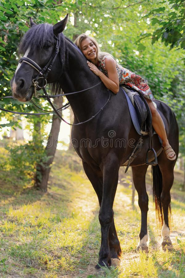 Young woman in a bright colorful dress riding a black horse. In the park royalty free stock photos