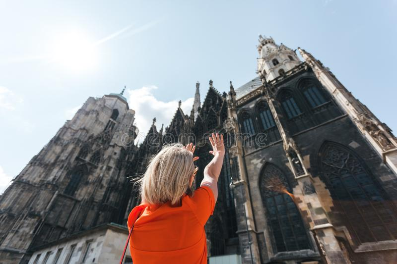 A young woman in a bright orange dress stands on the background of St. Stephen`s Cathedral in Vienna, Austria stock photography
