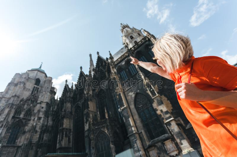 A young woman in a bright orange dress stands on the background of St. Stephen`s Cathedral in Vienna, Austria stock photo