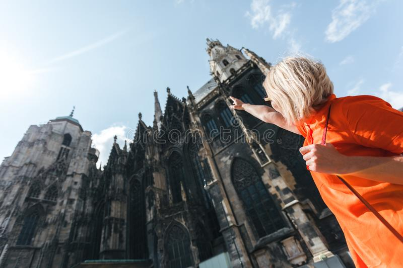 A young woman in a bright orange dress stands on the background of St. Stephen`s Cathedral in Vienna, Austria stock images