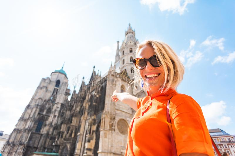 A young woman in a bright orange dress stands on the background of St. Stephen`s Cathedral in Vienna, Austria royalty free stock images