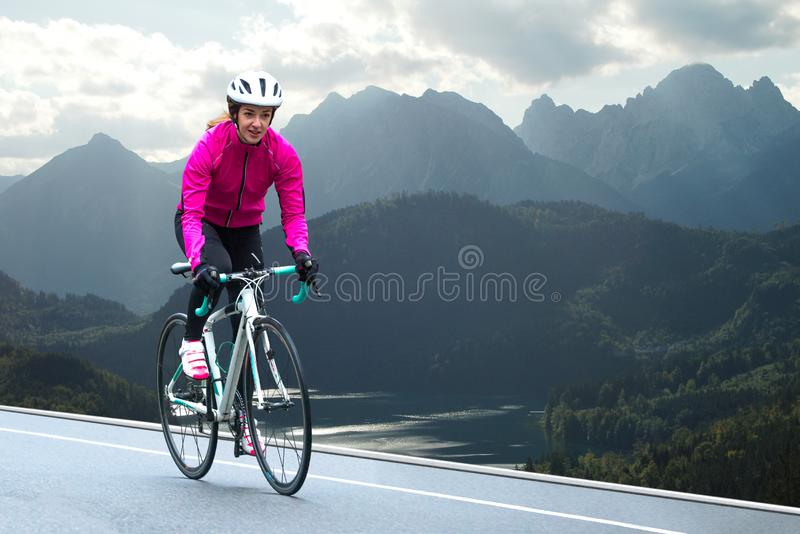 Young Woman in Bright Pink Jacket Riding Road Bicycle on Mountain Alpine Road. Healthy Lifestyle and Adventure Concept. Young Woman in Bright Pink Jacket Riding stock image