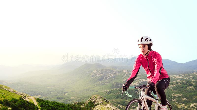 Young Woman in Bright Pink Jacket Riding Road Bicycle on Mountain Alpine Road. Healthy Lifestyle and Adventure Concept. Young Woman in Bright Pink Jacket Riding stock photo
