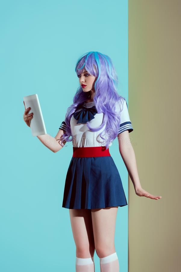 young woman in bright wig using digital tablet royalty free stock images