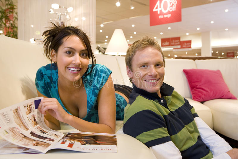 Young woman with brochure on sofa in shop by man, smiling, portrait stock photography