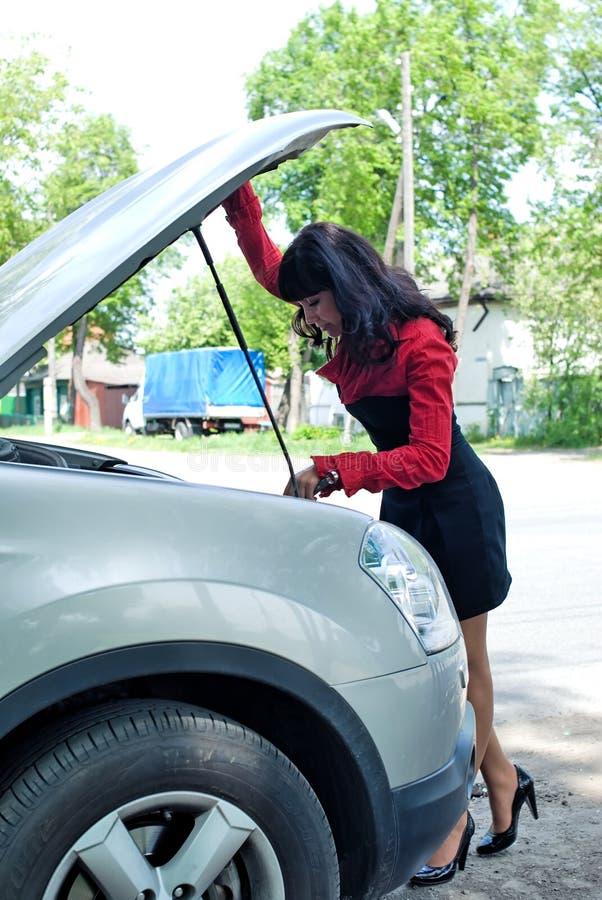 Young woman at broken car stock images