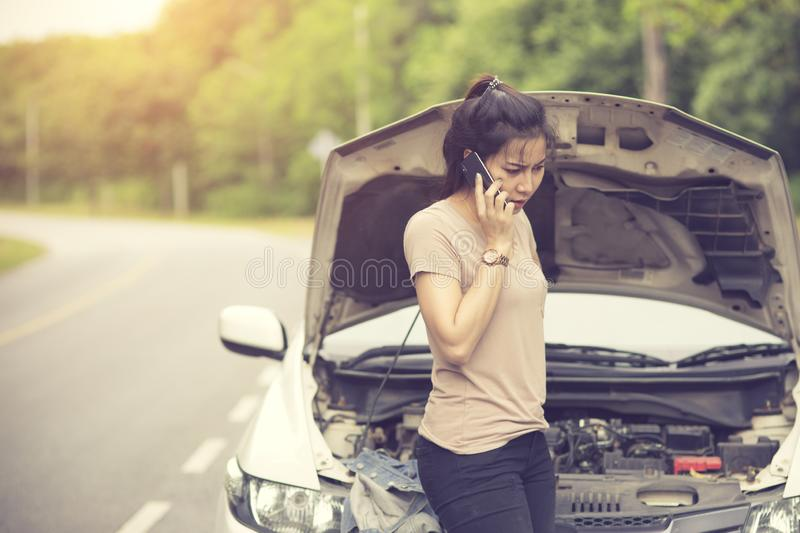 Young woman with broken car calling for help. Vintage color stock photos