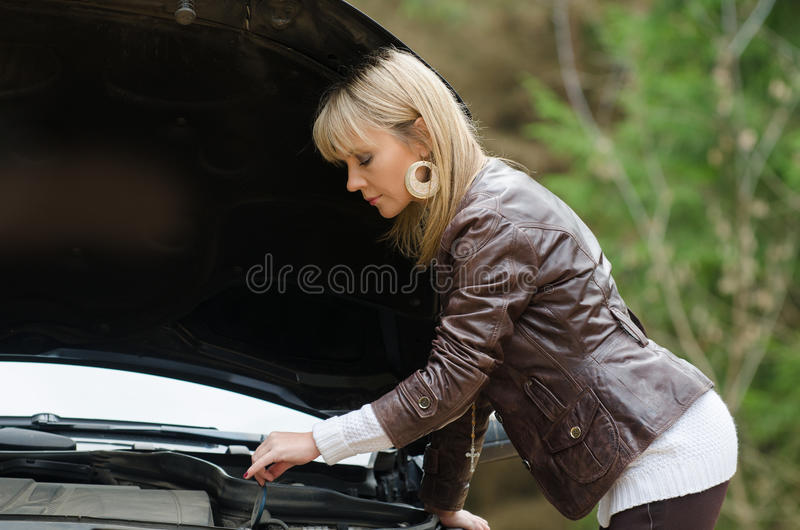 Young woman at broken car. In the forest stock photos