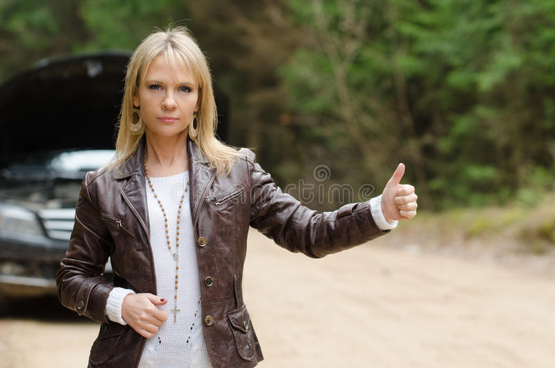 Young woman at broken car. Young woman hitchhiking at broken car in the forest royalty free stock photos