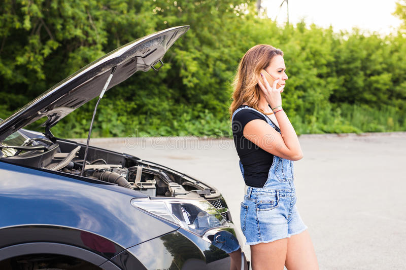 Young woman with broken down car with hood open call for help. Young brunette girl with broken down car with hood open call for help royalty free stock image