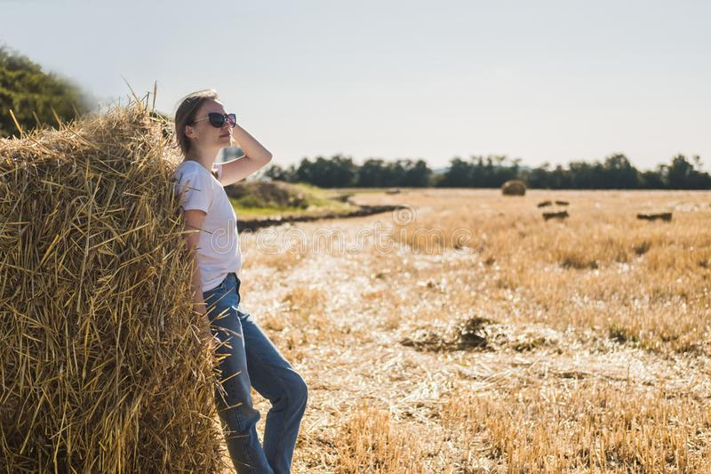 Young woman with brown hair in white T-shirt and blue jeans poses by haystack on a field after harvest. Warm sunset lighting stock images