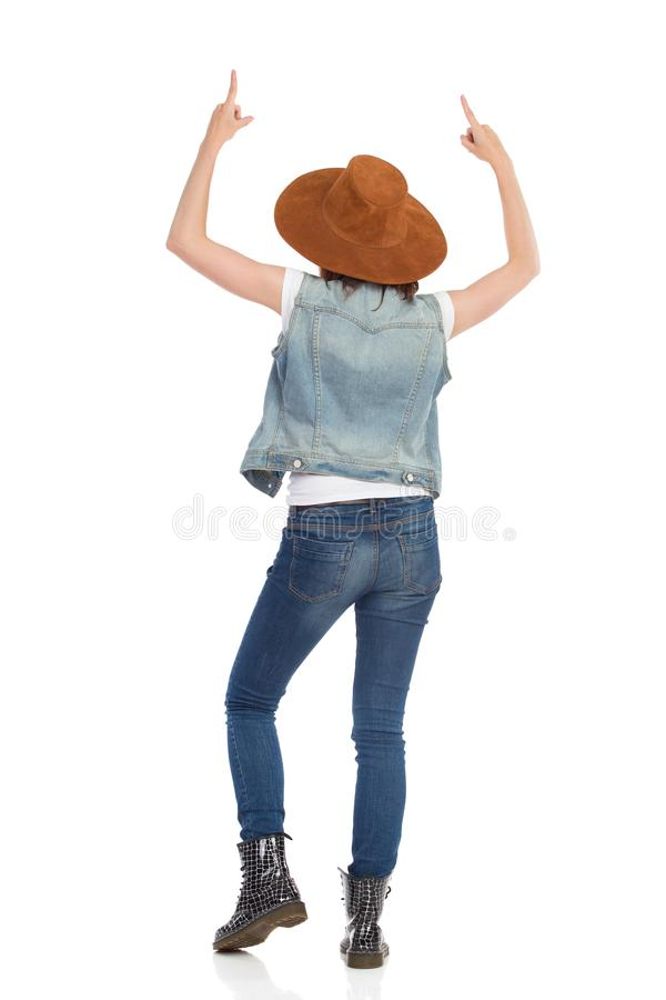Young Woman In Brown Hat And Jeans Vest Is Pointing Up. Rear View. Beautiful young woman in brown suede hat and jeans vest is standing and pointing up. Rear stock photo