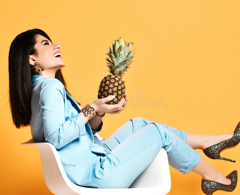 Young woman brunette in blue official suit and high heel shoes sitting in designer armchair with pineapple on yellow stock images
