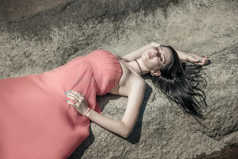 Young woman, brunette, caucasian, lying on a stone on the coast, in a pink dress stock photo