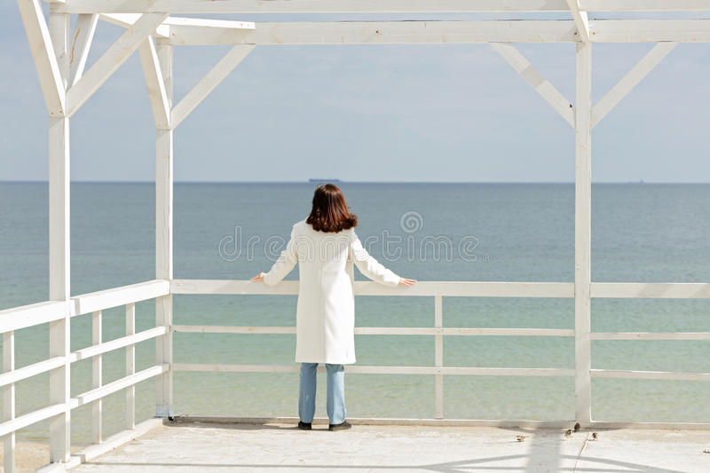 Young woman brunette in a white coat on the promenade near the stock images