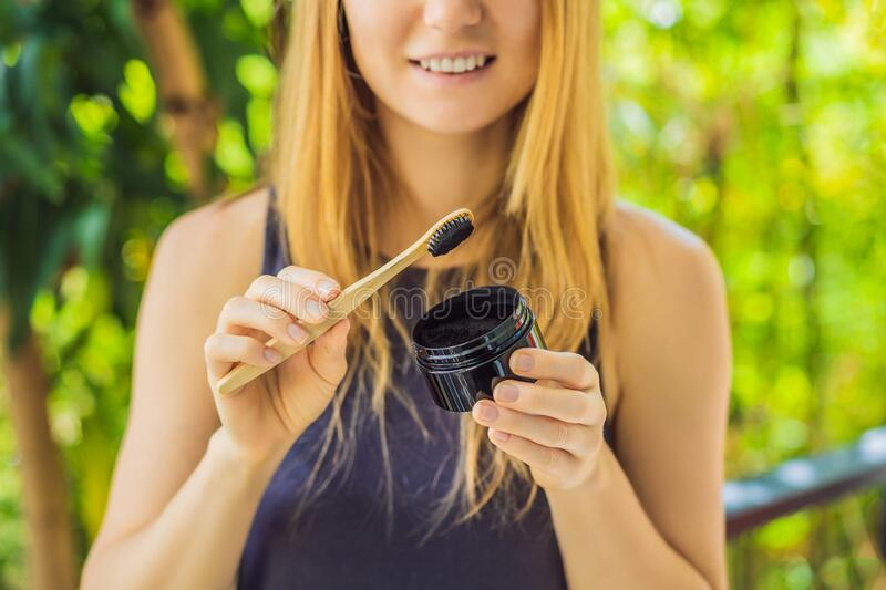 Young woman brush teeth using Activated charcoal powder for brushing and whitening teeth. Bamboo eco brush royalty free stock photography