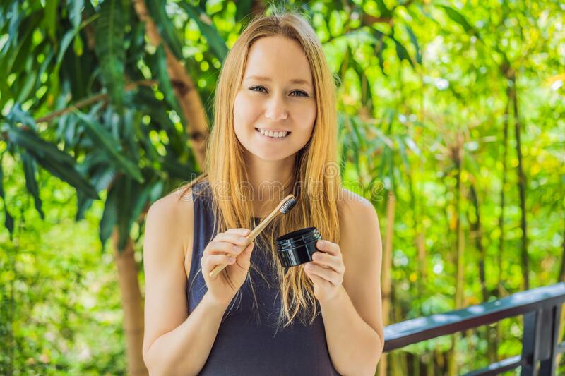 Young woman brush teeth using Activated charcoal powder for brushing and whitening teeth. Bamboo eco brush stock image