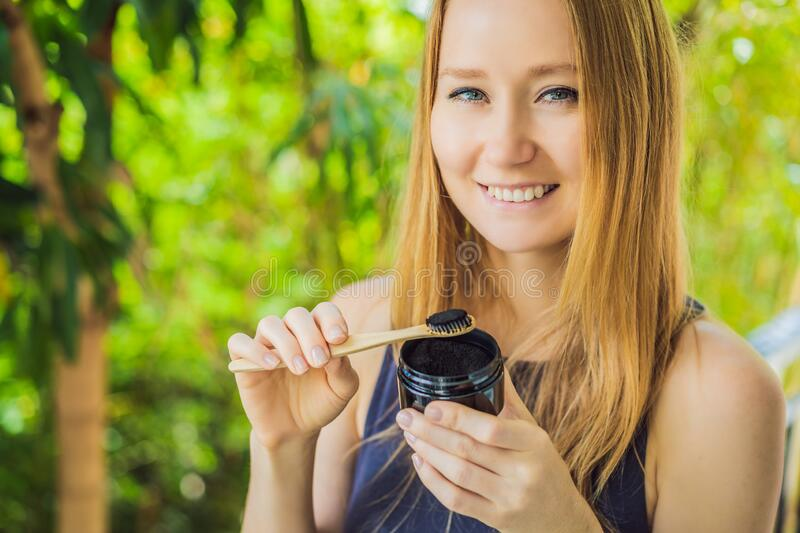 Young woman brush teeth using Activated charcoal powder for brushing and whitening teeth. Bamboo eco brush stock photos