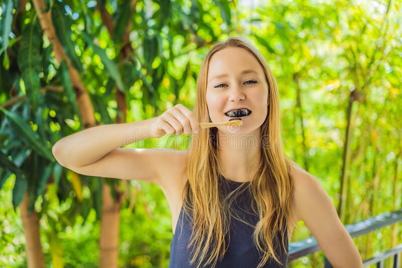 Young woman brush teeth using Activated charcoal powder for brushing and whitening teeth. Bamboo eco brush stock photography