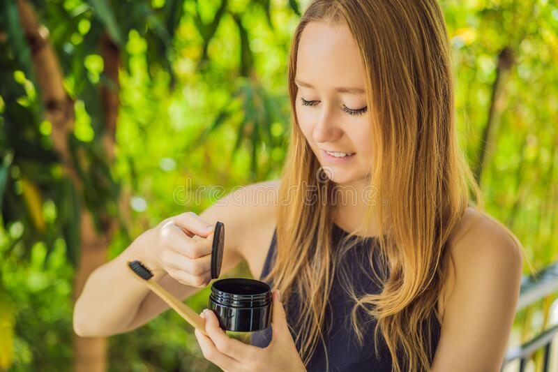 Young woman brush teeth using Activated charcoal powder for brushing and whitening teeth. Bamboo eco brush royalty free stock photos