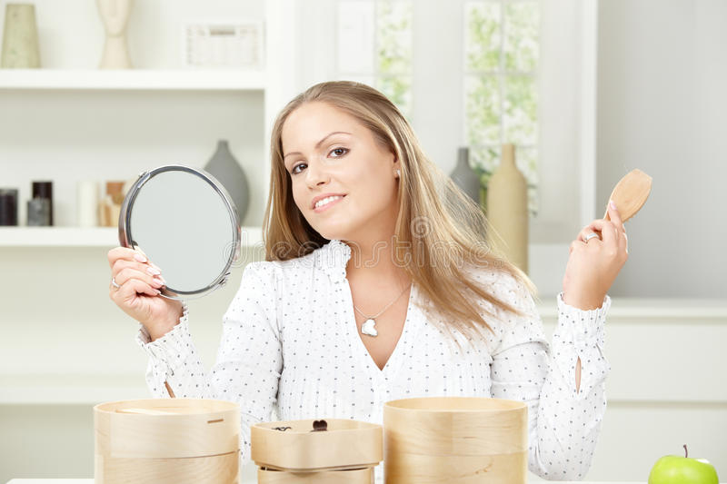 Young woman brushing hair. Beautiful young woman sitting at table, holding makeup mirror and brushing her hair, smiling royalty free stock images