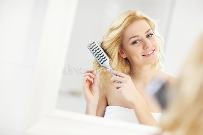 Young woman brushing hair. A picture of a happy woman brushing her hair in the bathroom stock photos