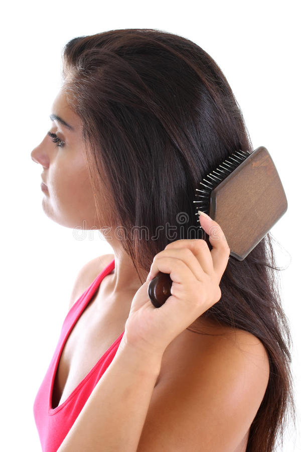 Young woman brushing her hair. Young pretty woman in pink brushing her hair stock image