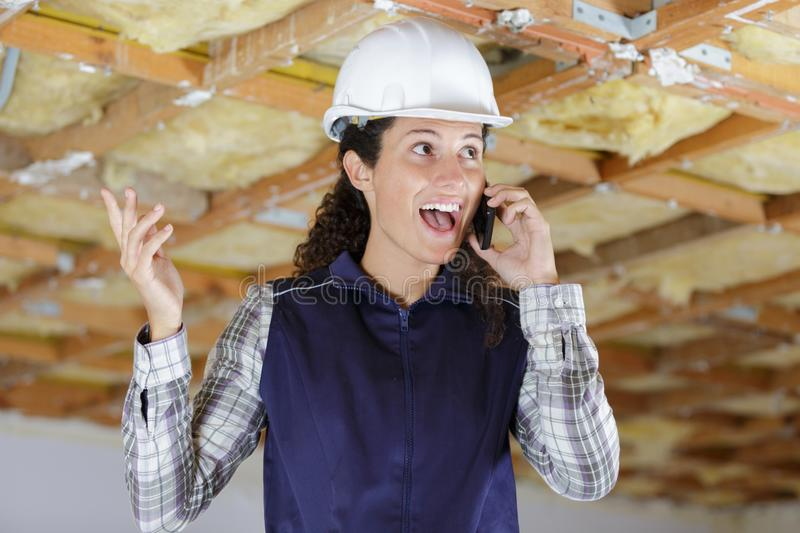 Young woman builder on phone stock photography