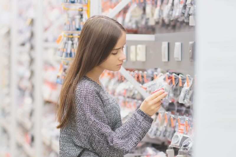 Young woman in a building materials store chooses a electric socket.  royalty free stock image