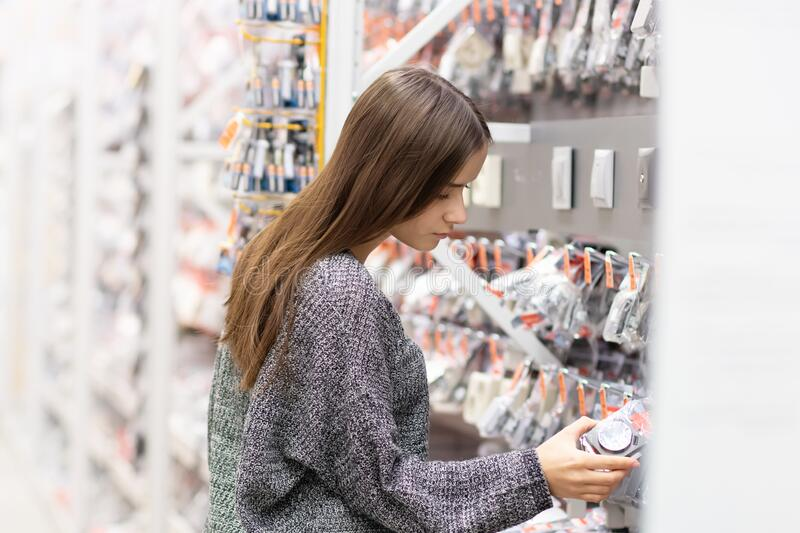 Young woman in a building materials store chooses goods.  royalty free stock photography