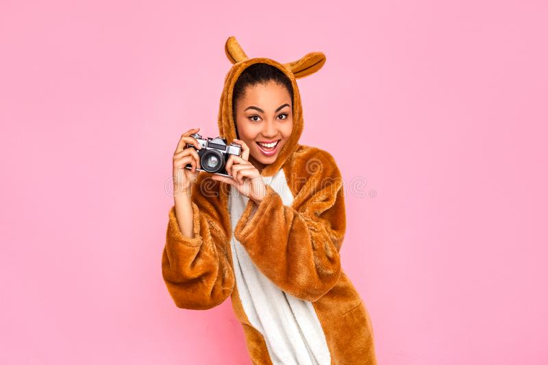 Freestyle. Young woman in kigurumi standing isolated on pink taking photos with camera smiling playful royalty free stock photography