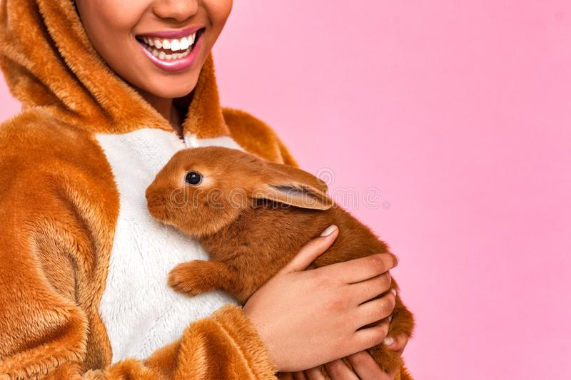 Freestyle. Young woman in kigurumi standing isolated on pink with rabbit close laughing cheerful close-up royalty free stock photography