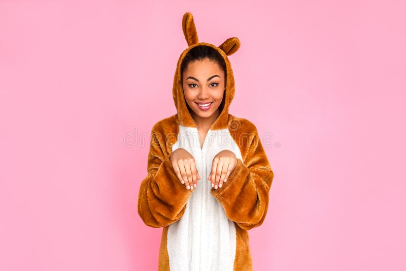 Freestyle. Young woman in kigurumi standing isolated on pink posint ot camera like rabbit smiling happy royalty free stock photo
