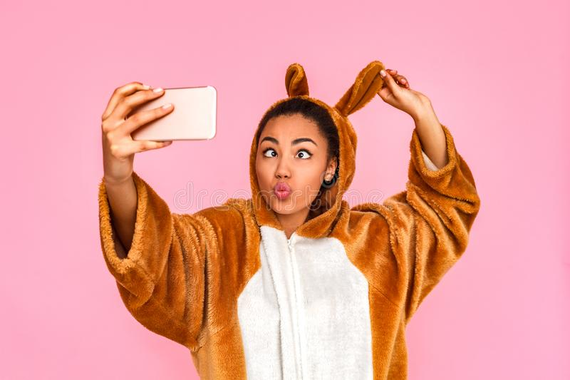 Freestyle. Young woman in kigurumi standing isolated on pink taking selfie on phone looking at nose touching rabbit ears stock photo