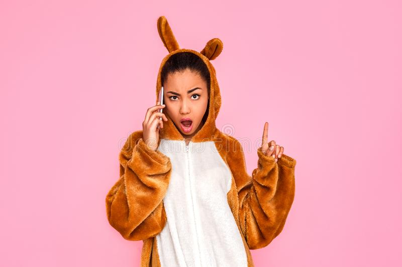 Freestyle. Young woman in kigurumi standing  on pink talking on phone looking camera sassy stock photo