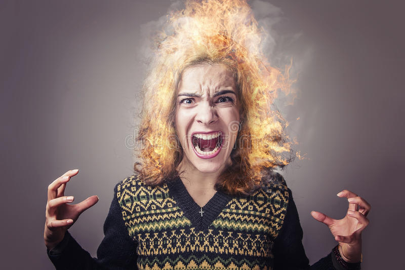 Young woman burning with rage. Enraged young lady screaming with her hair on stock image
