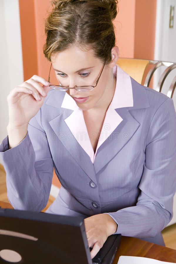 Young woman in business suit working from home. A young woman in business suit with glasses working from home royalty free stock image