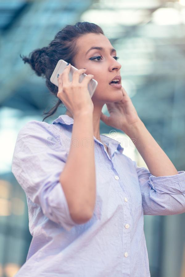 Young woman busy with calling, chatting on the cell phone side view portrait. royalty free stock images