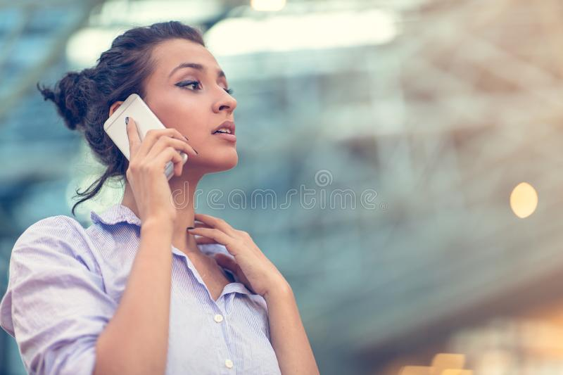 Young woman busy with calling, chatting on the cell phone side view portrait. stock photography