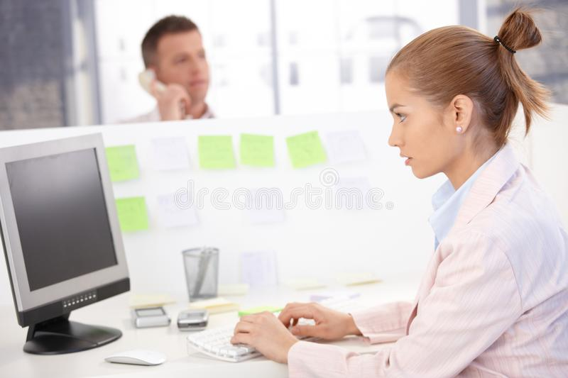 Young woman busy in office using computer stock photos